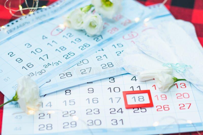 Calendario di mestruazione con i tamponi del cotone ed i cuscinetti sanitari Giorni critici della donna, protezione di igiene del fotografie stock libere da diritti