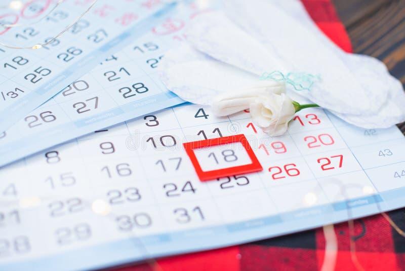 Calendario di mestruazione con i tamponi del cotone ed i cuscinetti sanitari Giorni critici della donna, protezione di igiene del fotografie stock