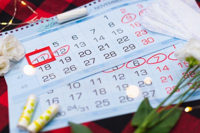 Calendario di mestruazione con i tamponi del cotone ed i cuscinetti sanitari Giorni critici della donna, protezione di igiene del immagine stock