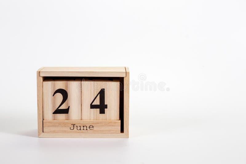 Calendario 24 giugno di legno su un fondo bianco fotografie stock