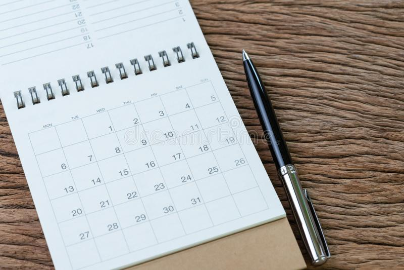 Calendario limpio blanco con la pluma en fondo de madera de la tabla usando para el recordatorio del negocio, el horario de viaje imagenes de archivo