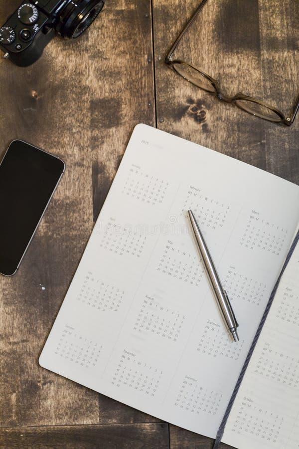 Calendario, teléfono móvil, cámara y vidrios en una tabla imágenes de archivo libres de regalías