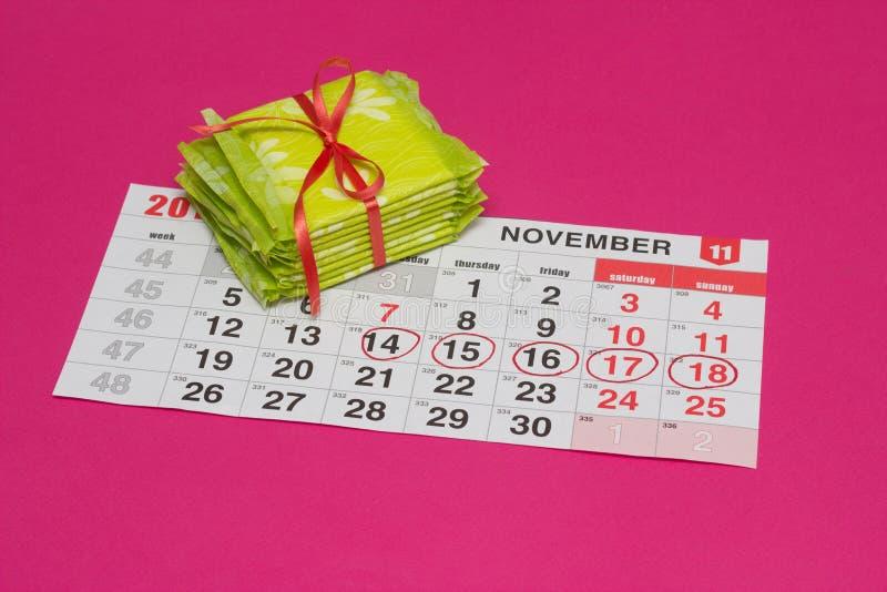 Calendrier avec des jours identifiés par un stylo feutre rouge et une pile de protections, fond rose, fréquence de règles, l'espa photographie stock libre de droits