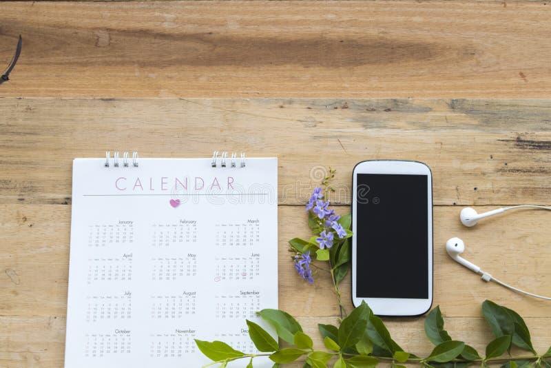 Calendrier avec le bureau de téléphone portable pour le travail d'affaires photo libre de droits