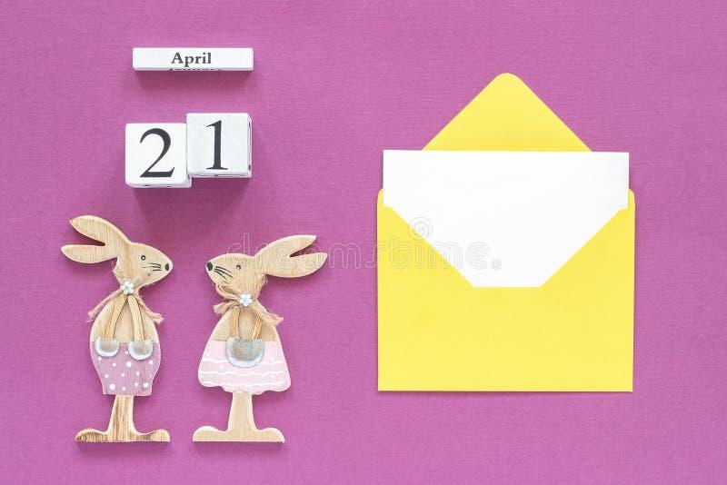 Calendrier 21 avril, lapins de Pâques en bois de paires, enveloppe jaune avec la carte vierge sur le concept de papier pourpre Pâ image libre de droits