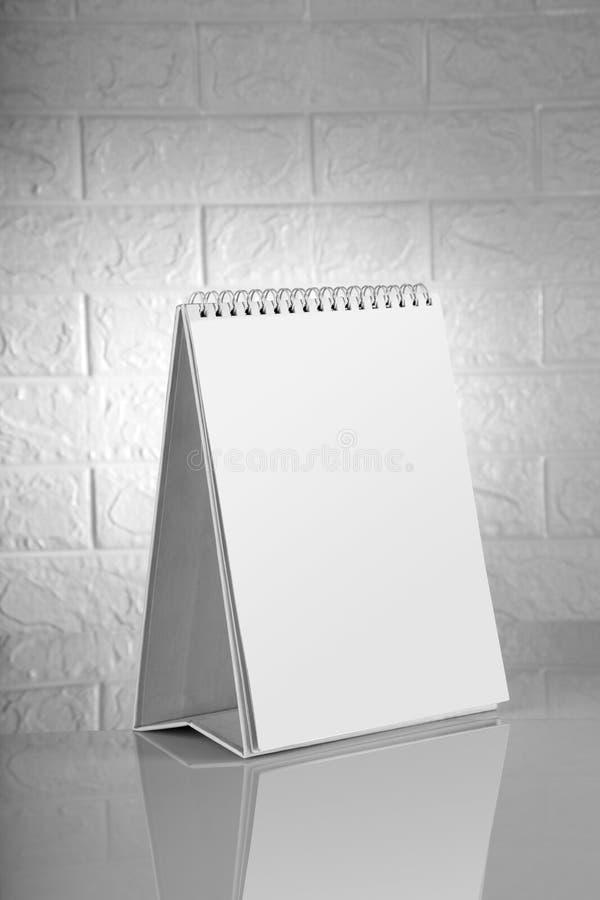 Calendrier blanc vide pour des maquettes sur le fond de mur de briques photo stock