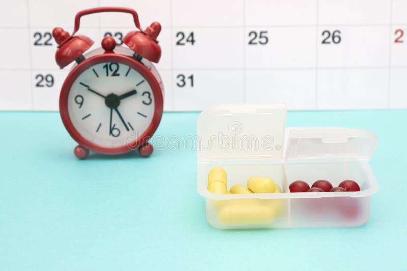 Calendrier, horloges et pilules jaunes dans la boîte de pilule Pharmaceutique, comprimés et capsules jaunes, réveil rouge PH conc photographie stock libre de droits