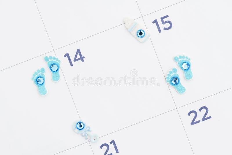 Calendrier mensuel avec les empreintes de pas minuscules, la bouteille et le hochet de bébé image libre de droits