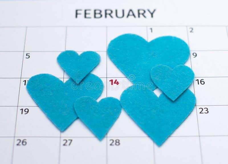Calendrier pour le jour de valentines avec le foyer sur 14 avec la vue supérieure sentie bleue de coeurs photographie stock
