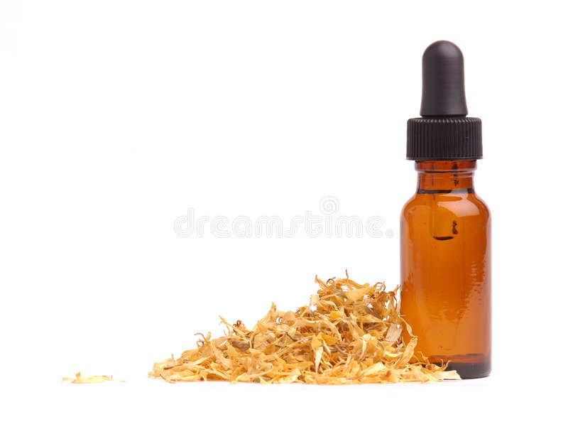 Calendula Aromatherapy. Bottle of Calendula oil with calendula petals stock photos