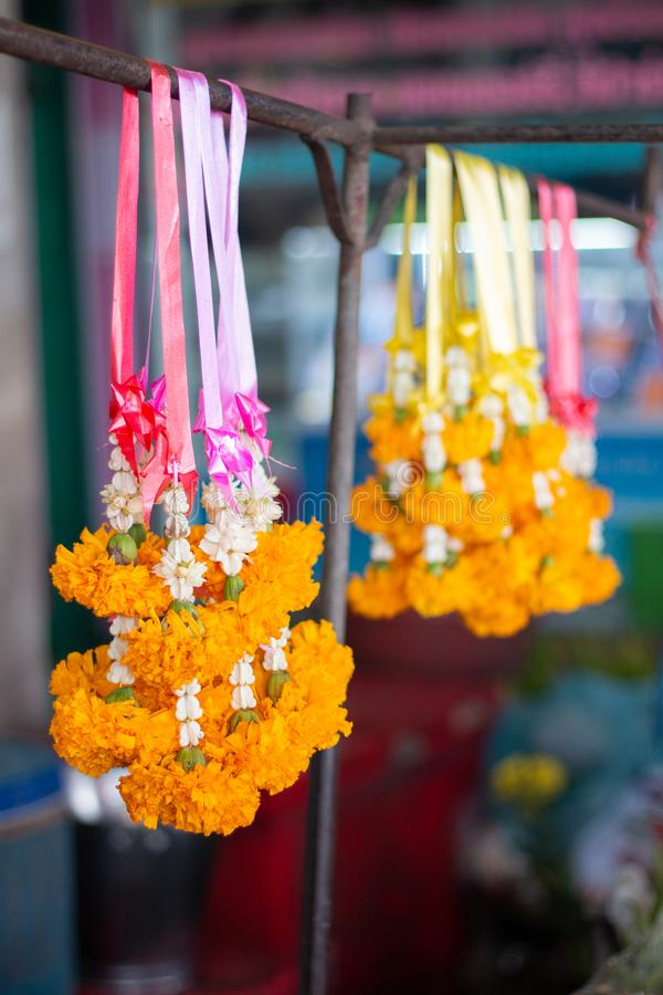 Calendula flower , yellow flower steering or garland hanging at market for worship and prayer with buddha in thai religion traditi stock images
