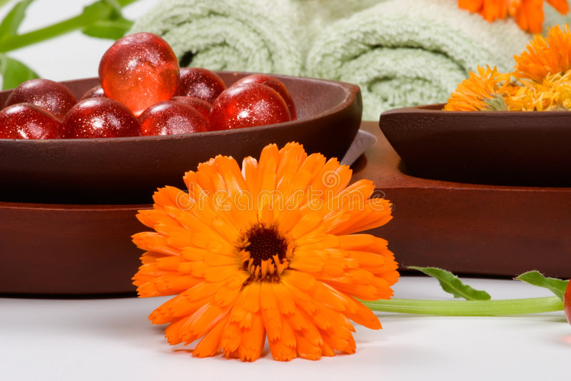 Calendula spa set. Fresh marigold spa set with fresh and dried flowers, aromatic oil balls and towels. Best suited for relaxing and health commercials stock images