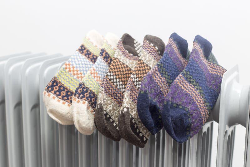 Calentador de aceite que seca tres pares de calcetines coloridos en el fondo blanco fotos de archivo