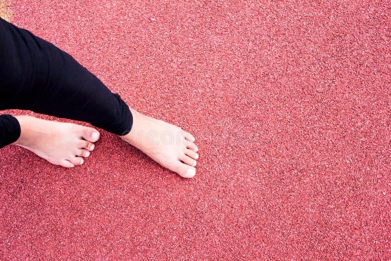 Calentamiento del atleta de sexo femenino en la arena y la pista corriente t del estadio de la raza fotografía de archivo