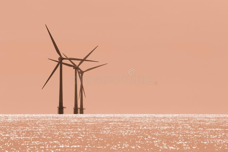 Calentamiento del planeta Turbinas costeras del parque eólico con el cielo anaranjado crepuscular foto de archivo