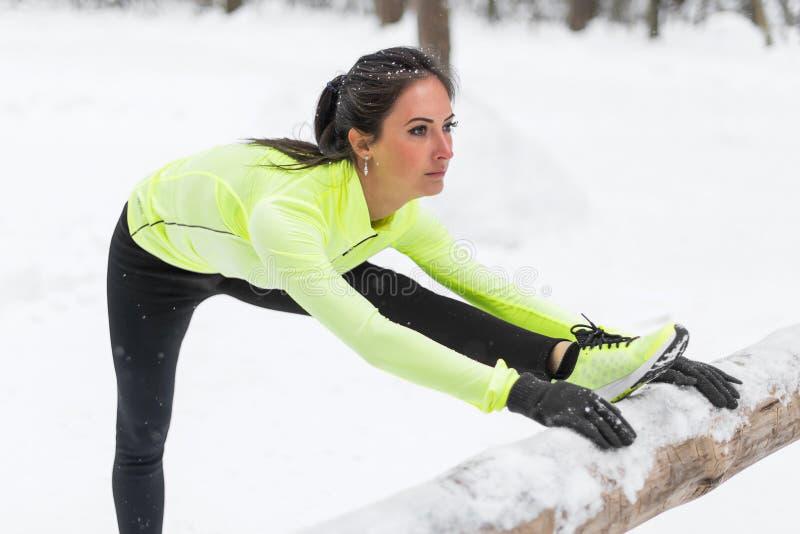 Calentamiento modelo del atleta de la aptitud que estira sus tendones de la corva, pierna y detrás Mujer joven que ejercita al ai foto de archivo