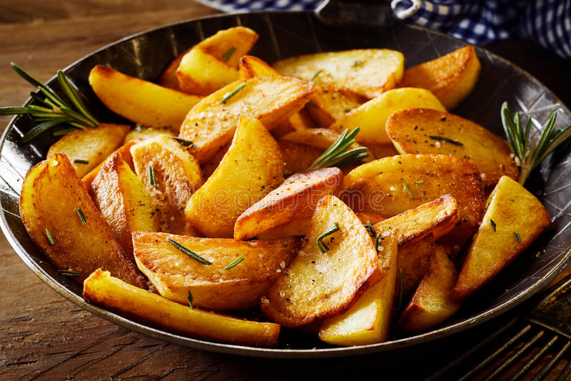 Cales frites croustillantes savoureuses de pomme de terre avec le romarin image libre de droits