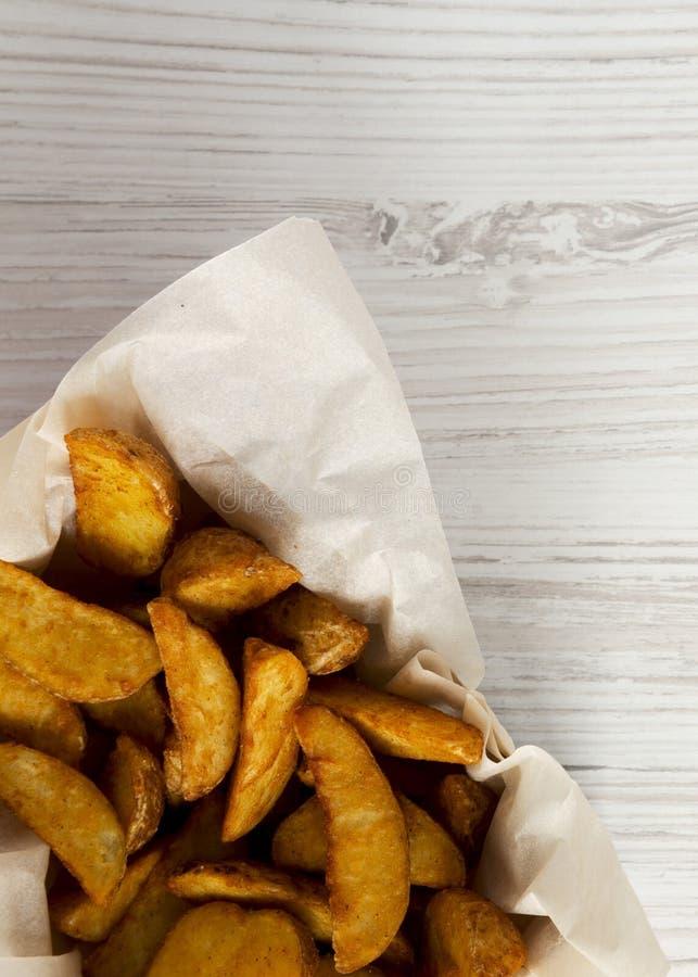 Cales frites de pomme de terre dans la boîte de papier sur une table en bois blanche Vue aérienne et supérieure, d'en haut photographie stock