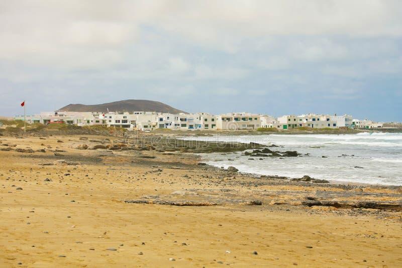 Caleta de Famara παραλία και χωριό στο υπόβαθρο, Lanzarote, Κανάρια νησιά στοκ εικόνες