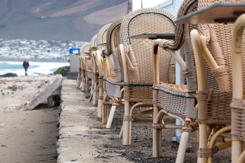 Caleta de Famara/SPAIN - 2-ое февраля 2018: Стулья и таблицы пустого внешнего ресторана с морем на заднем плане стоковое фото