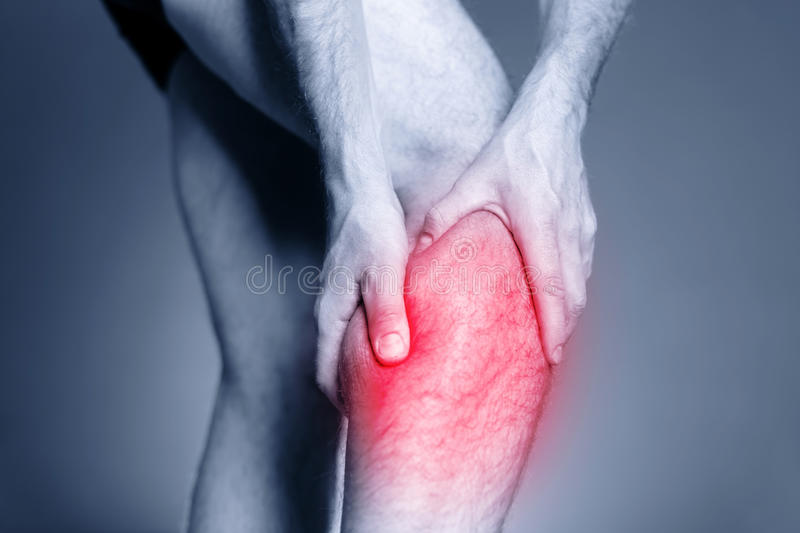 Calf leg pain, muscle injury. Calf leg pain, man holding sore and painful muscle, sprain or cramp ache filled with red pink bright place. Person injured when stock photography