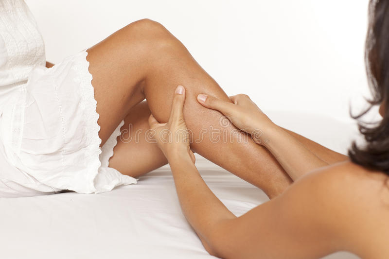 Calf muscle massage. Massage of a women calf muscle on white background royalty free stock photos