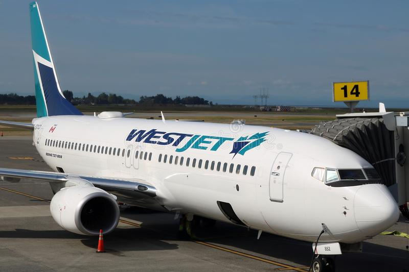 Westjet commercial airplane at loading ramp on a sunny day in Toronto Airport stock image