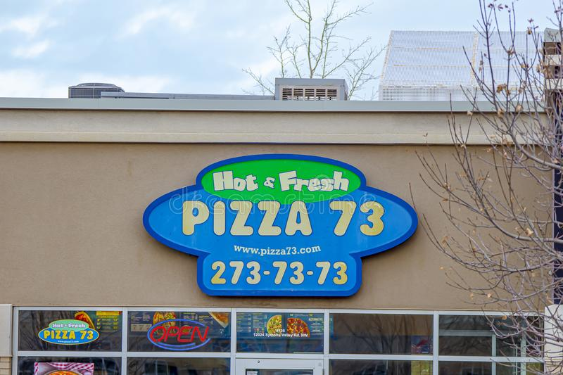 A close-up of a Pizza 73 sign . popular chain 'Pizza 73' just revealed new plant-based. Calgary, Alberta. Canada Jan 4 2020. A close-up of a Pizza royalty free stock photos