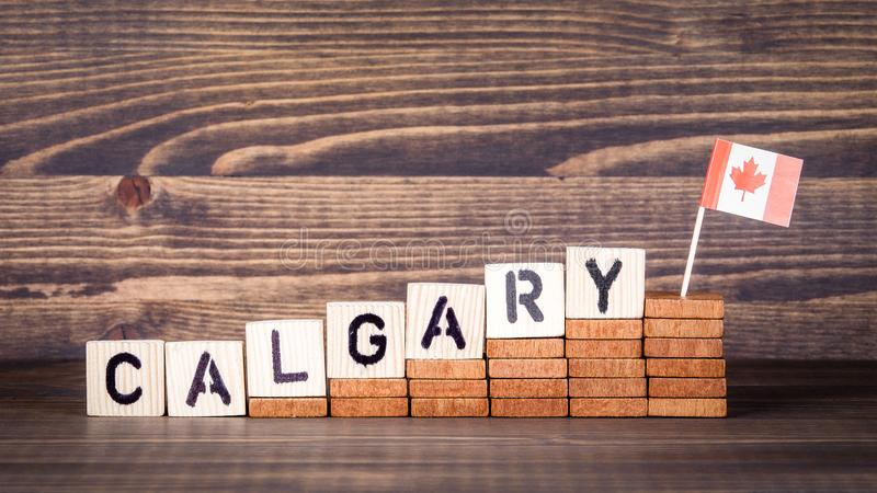 Calgary Canada. Politics, economic and immigration concept. Wooden letters and flag on the office desk stock images