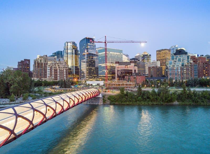 Calgary downtown with iluminated Peace Bridge, Alberta, Canada. Calgary downtown with iluminated Peace Bridge and full moon, Alberta, Canada stock image
