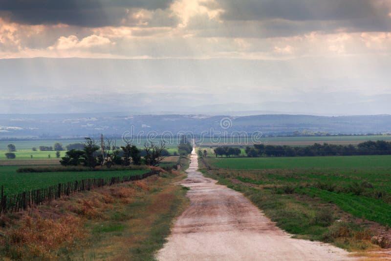 A calha rural da estrada coloca ir ao horizonte, à luz solar e às nuvens imagem de stock
