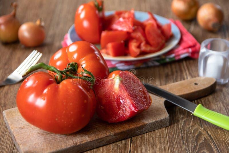Cali i pokrojeni pomidory na ceramicznej talerza i ca?ej cebuli w tle obraz royalty free