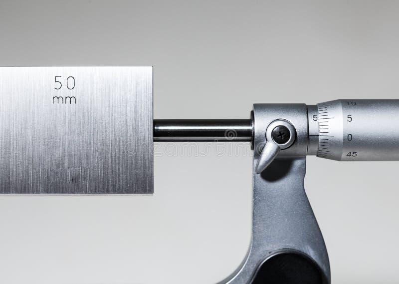 Calibración fuera del micrómetro con el bloque de indicador fotos de archivo