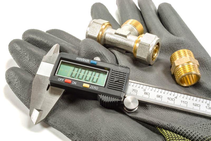 Calibrador de Digitaces con las colocaciones de la fontanería y los guantes del funcionamiento en un fondo blanco imágenes de archivo libres de regalías