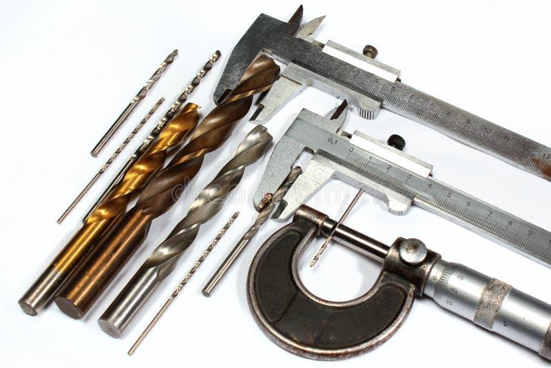 Calibrador de las brocas y del tornillo de micrómetro en el fondo blanco imagen de archivo