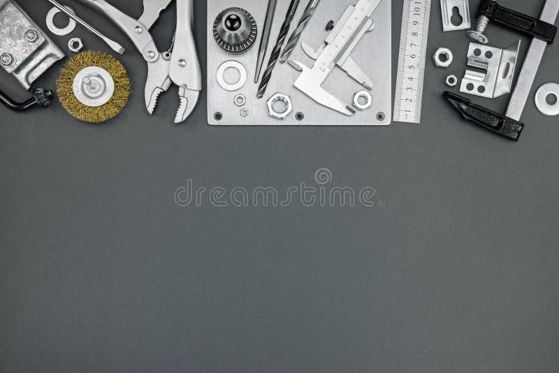 Calibrador del abrazadera, a vernier, regla, taladro y otras herramientas en vagos grises foto de archivo