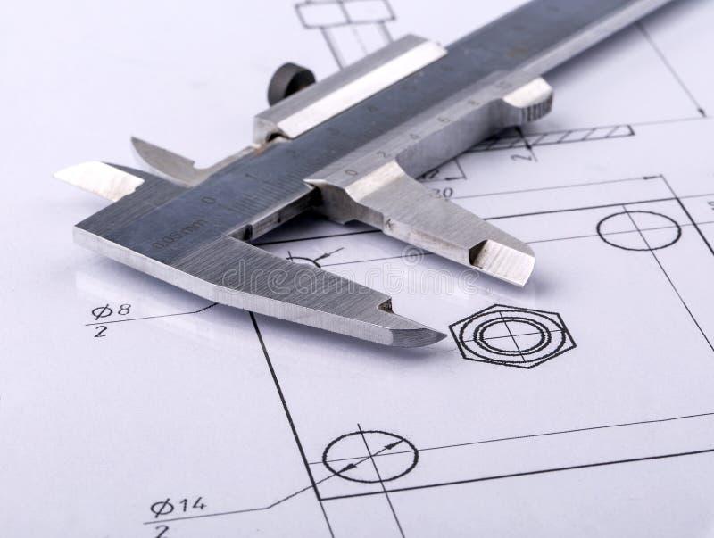Calibrador del metal y dibujo de ingeniería viejos imagen de archivo