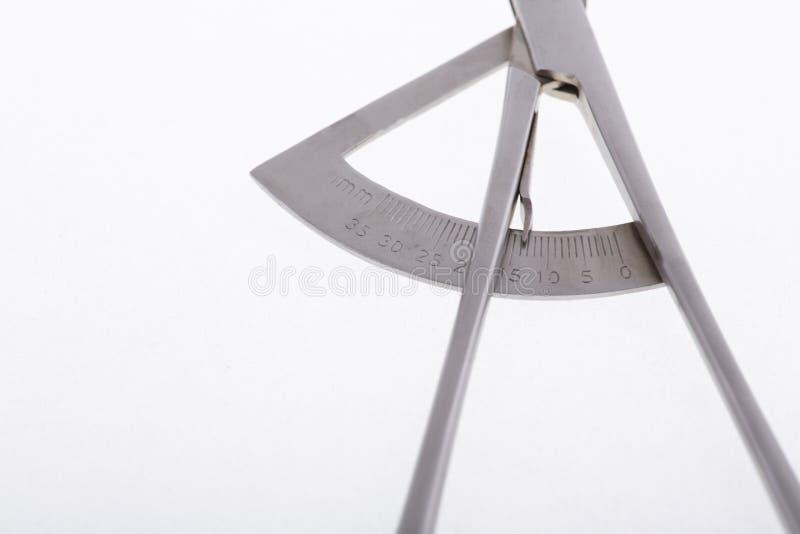 Calibrador dental en el fondo blanco Este instrumento ha calibrado la escala y se utiliza para medir el tamaño de dientes primer foto de archivo libre de regalías