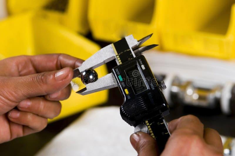 Calibrador que mide una bola del hierro fotografía de archivo libre de regalías