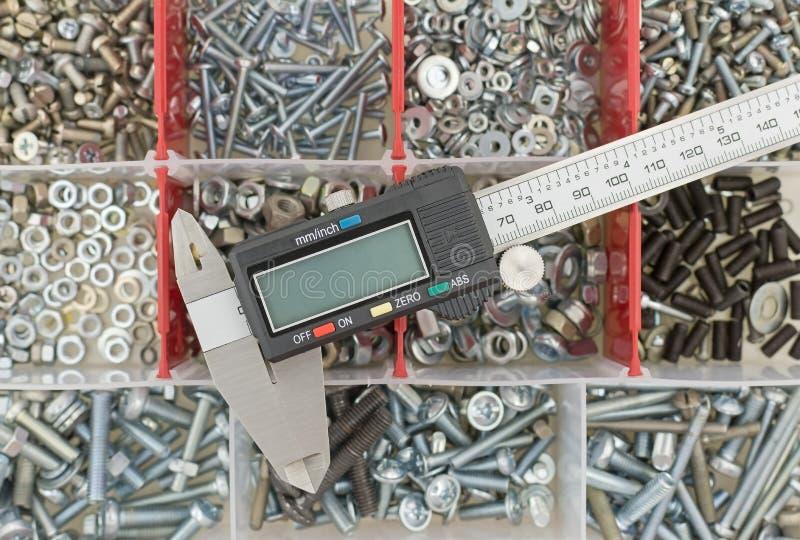 Calibrador a vernier contra los tornillos y las nueces del fondo imagenes de archivo