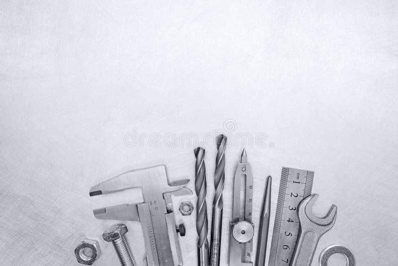 Calibrador a vernier, taladros, pernos, alicates y tornillos en b rasguñado imagen de archivo