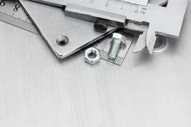 Calibrador a vernier, tornillos y perno en fondo rasguñado del metal fotos de archivo libres de regalías