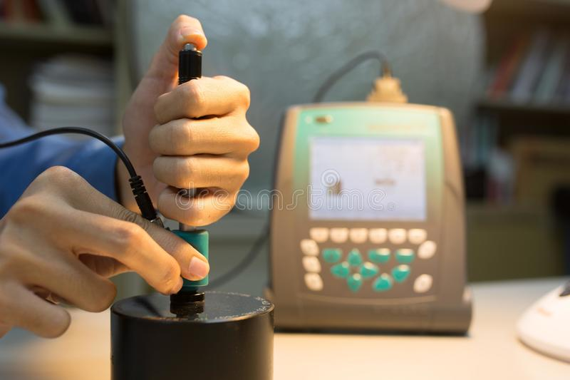 Calibration digital hardness tester with standard block. In warm light stock photography