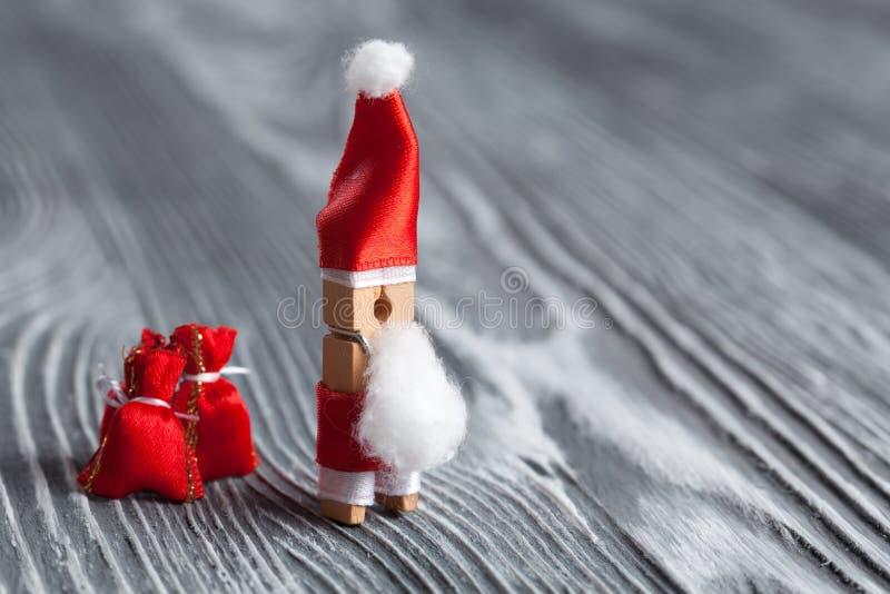 Calibre de carte postale de Joyeux Noël et de bonne année Pince à linge en bois Santa Claus avec le sac de cadeau de Noël Gris te image stock