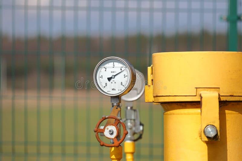 Calibre de pressão para medir a pressão do gás natural em um gasoduto Tubulações amarelas do transporte na superfície da cerca foto de stock