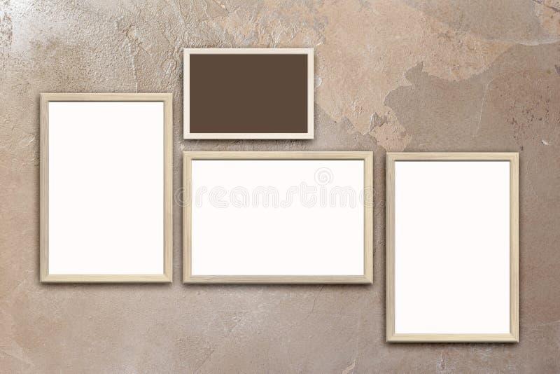 Calibre des affiches vides dans les cadres en bois sur le mur brun texturisé de stuc photos libres de droits