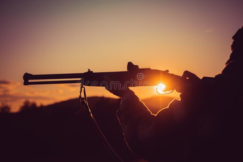 Calibri dei fucili di caccia Fucile Hunter Silhouetted nel bello tramonto Siluetta del cacciatore Ha tirato l'innesco immagini stock