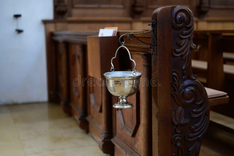 Calice avec de l'eau saint à la croix sur entrer dans une église photo libre de droits
