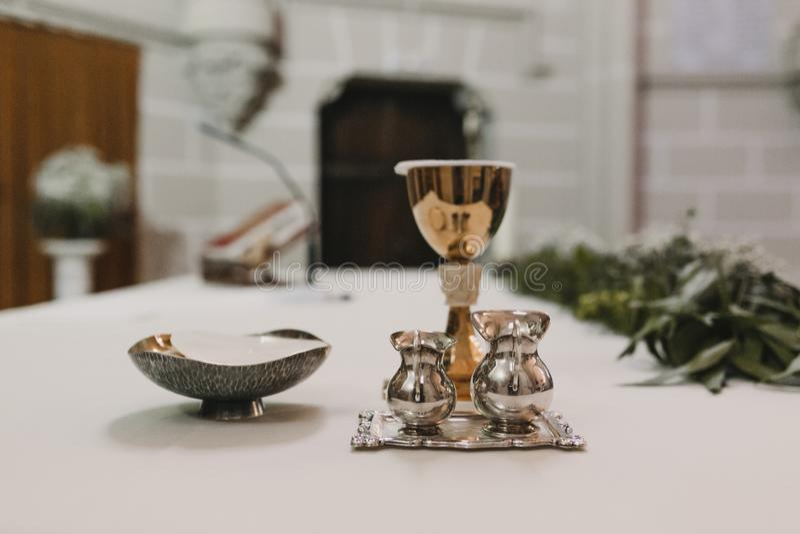 Calice di vino sulla tavola durante la massa nuziale di cerimonia di nozze Concetto di religione Ornamenti cattolici del eucharis fotografia stock