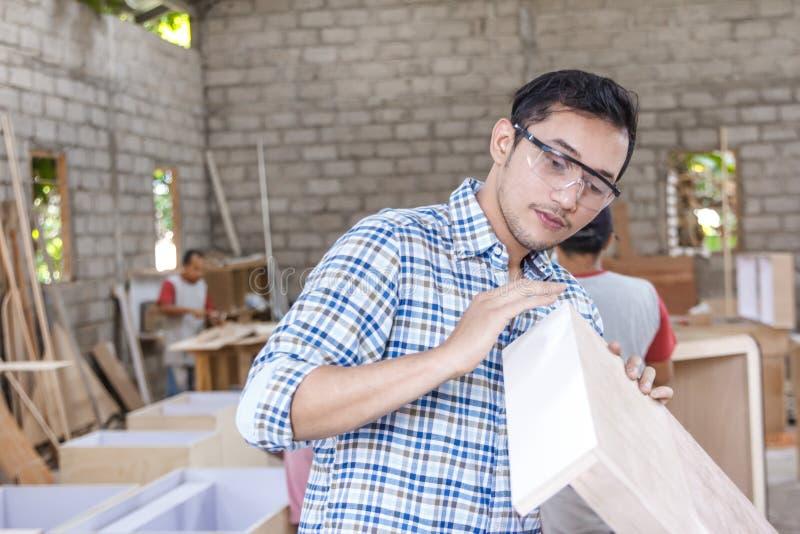 Calidad joven del carpintero que controla su producto imagen de archivo libre de regalías